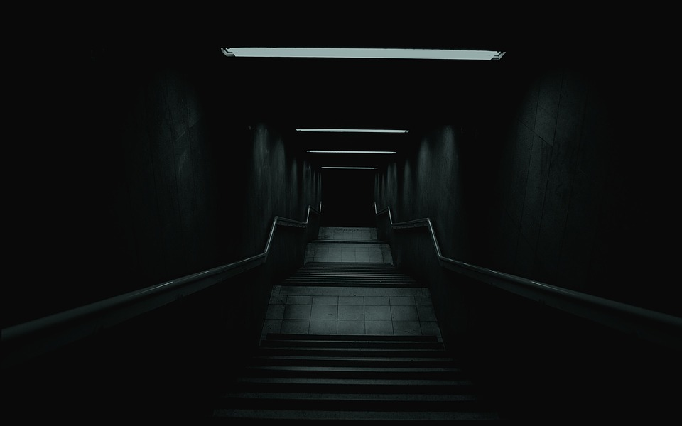 Spooky stairs leading into a dark basement.